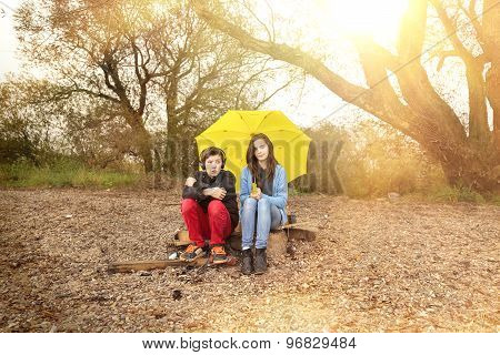 Two Teenager With Umbrella Sitting On A Dirty Beach With Sun In Background