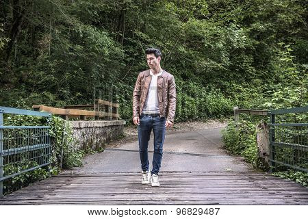 Handsome athletic young man hiking on bridge in forest