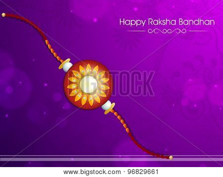Beautiful creative rakhi on floral design decorated purple background for Indian festival, Raksha Bandhan celebration.