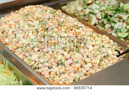 Russian salad in gastronomical containers in shop or restaurant