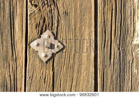 Rusty rivet in wooden door