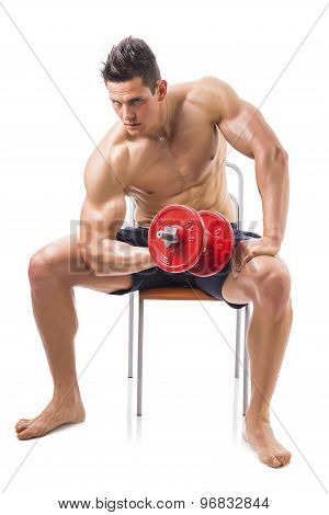 Muscular shirtless young man exercising biceps with dumbbell