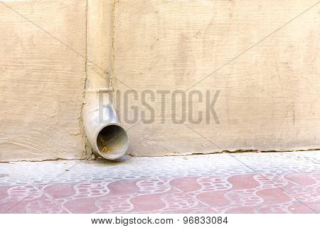 Rainwater drain in a yellow wall