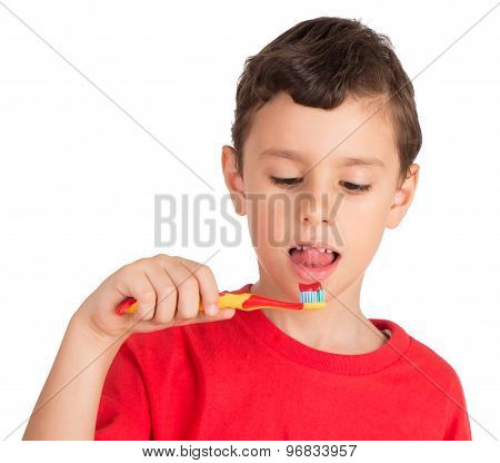 Young boy happily holding a tooth brush trying to lick tooth paste