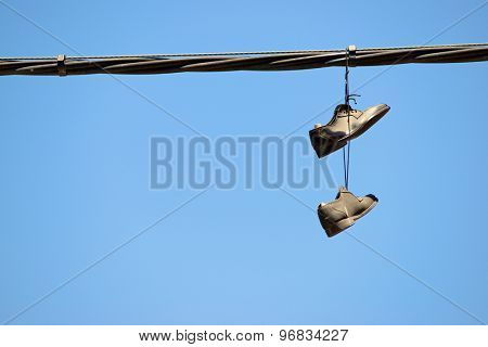 Pair of stylish shoes hanging from a cable.