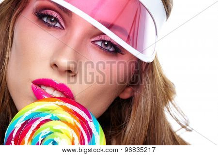 Glamourous girl wearing plastic cap holding lollipop
