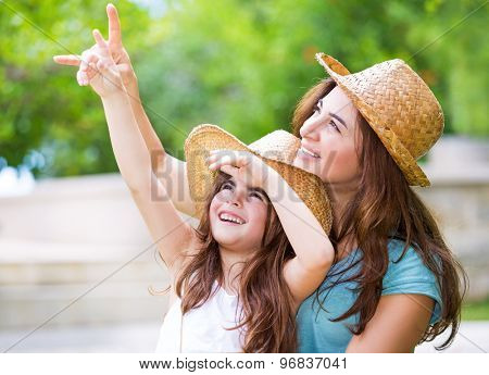 Happy mother and daughter spending time together outdoors, pointing fingers and enthusiastically looking up, with pleasure spending time in countryside