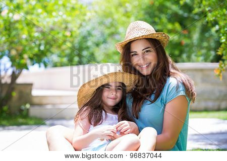 Happy family outdoors, cute cheerful mother with little daughter wearing identical straw hats and having fun on backyard