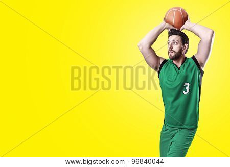Basketball Player on a green uniform on yellow background