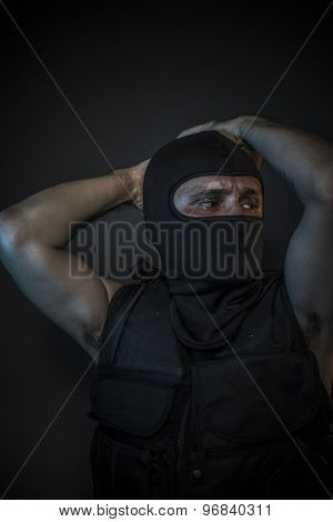 Man wearing balaclavas and bulletproof vest with firearms