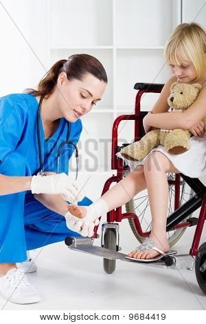 nurse bandaging little girls ankle