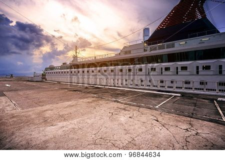 cruise ship and empty dock  at sunset