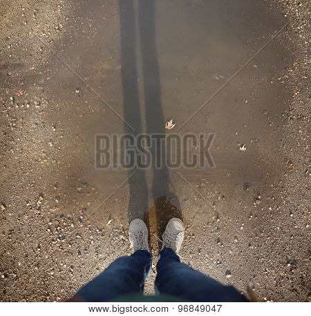 wide angle overhead shot of yellow and white boat or deck shoes in a muddy puddle with a long shadow of the legs