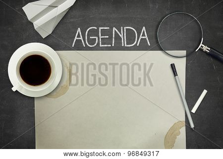 Agenda concept on black blackboard with empty paper sheet
