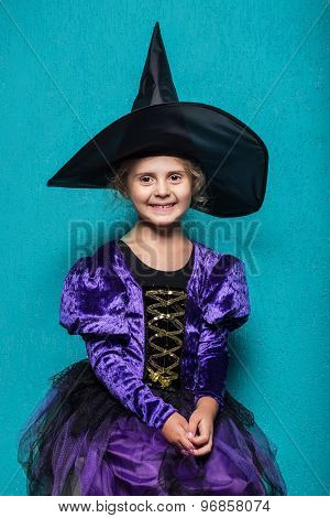 Portrait of little girl in black hat and witch clothing. Halloween. Fairy. Tale. Studio portrait