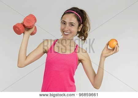 Fit Woman Showing An Apple And Dumbbells