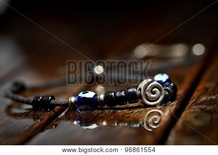 Hand made necklace on wodden wet background
