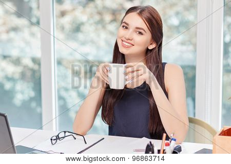 Upbeat business woman drinking coffee