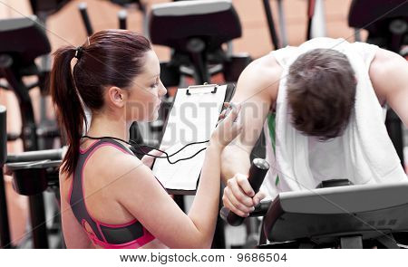 Female Coach Using A Chronometer While Man Is Pedaling On A Bicycle