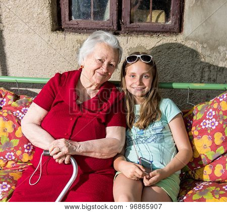 Grandmother And Granddaughter Sitting On The Bench
