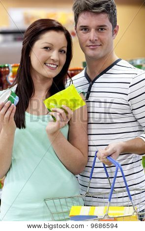 Portrait Of A Young Couple Buying Cans Standing In A Grocery Shop