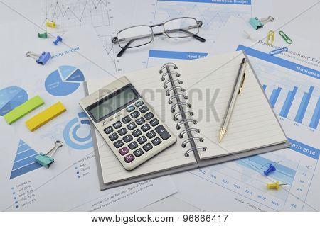 Book, Pen, Calculator, Glasses On Financial Chart