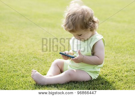 Little Boy On Grass With Phone