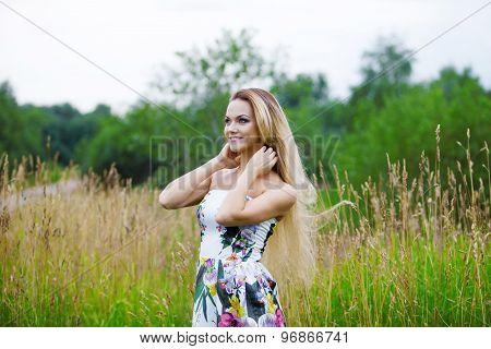 blond girl in dress  on a meadow