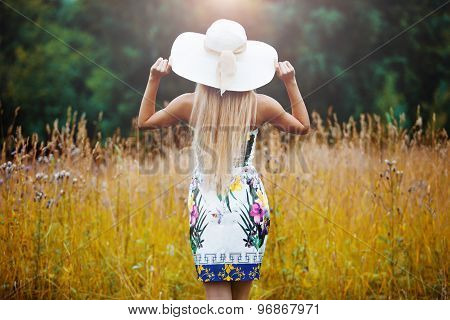 Beauty women Outdoors enjoying nature. Girl in a straw hat, back