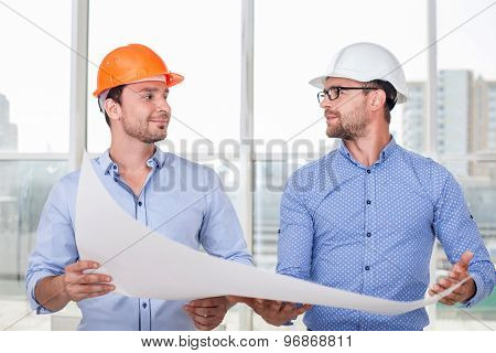 Cheerful young builders are discussing a new project