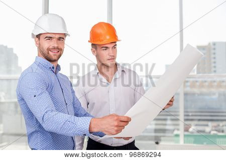Cheerful young builders are looking at sketches of building