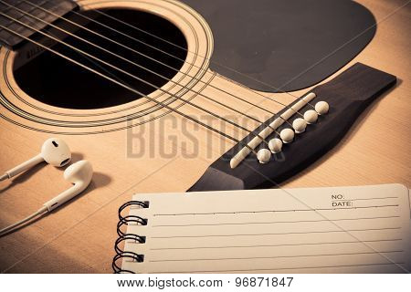 Notebook And Headphone On Guitar Background