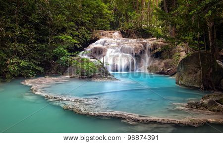 Mountain river stream flows through tropical forest and falls from cascades and waterfalls in wild lake with blue water