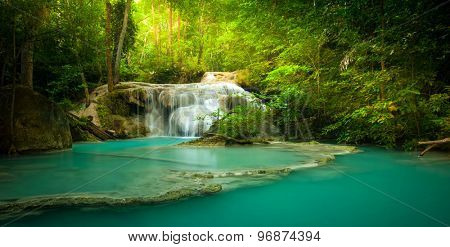 Waterfall in forest with sunlight beams and rays through trees and green leaves