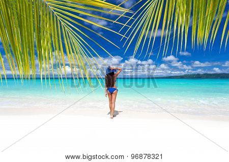Beautiful Woman On Beach. View Through Palm Tree Leafs