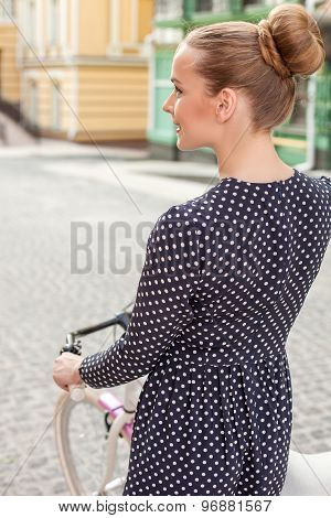 Attractive young girl is cycling in city