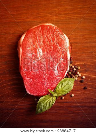 fresh raw steak with pepper and basil on the wooden board.Filtered image: warm cross processed vintage effect.