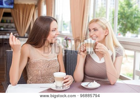 Pretty young girls are relaxing in restaurant