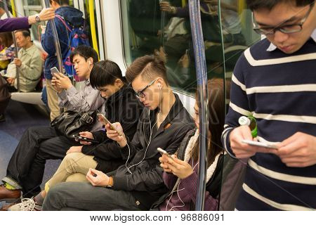 HONG KONG - CIRCA FEBRUARY, 2015: People traveling in the subway and actively use smartphones. Metro aka MRT is the most popular form of public transport in Hong Kong.