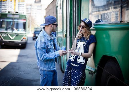 stylish couple with drinks near transport, bus, retro