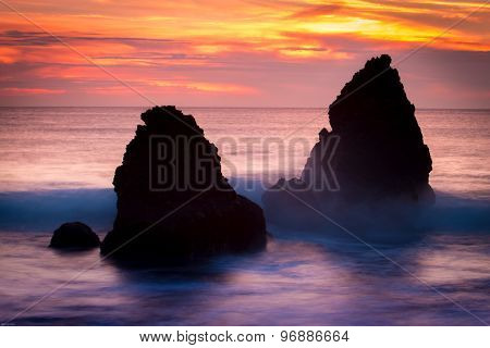 Silhouette of rocks in the sea a sunset