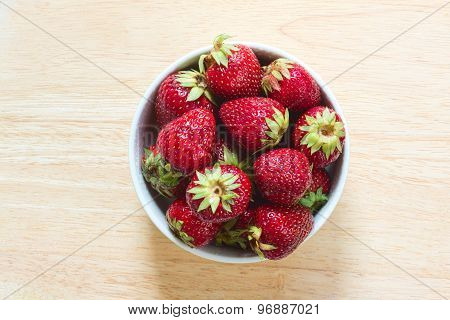 Strawberries in the ceramic bowl on the wooden plate