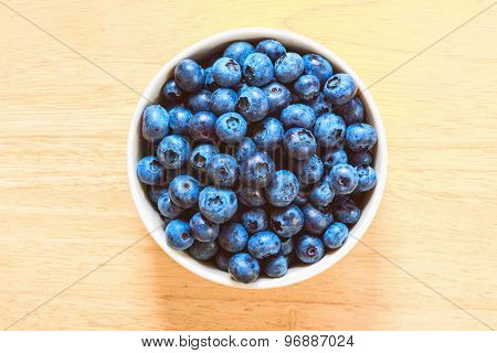 Blueberries in the ceramic bowl on the wooden plate