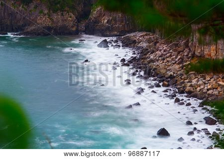 Volcanic rocky coast with storming sea