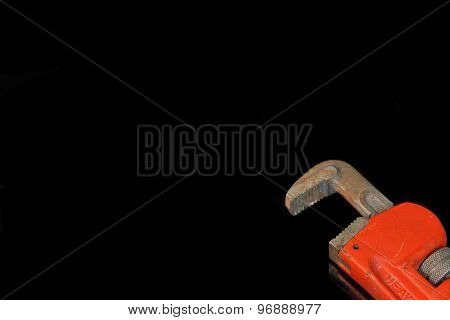 Large Adjustable Wrench With Red Handle Isolated On Black