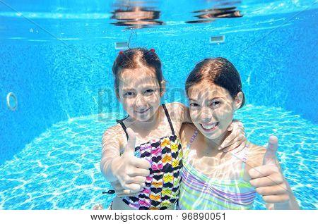 Children swim in pool underwater, happy active girls have fun in water, kids sport