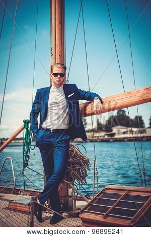 Stylish wealthy man on a luxury wooden regatta
