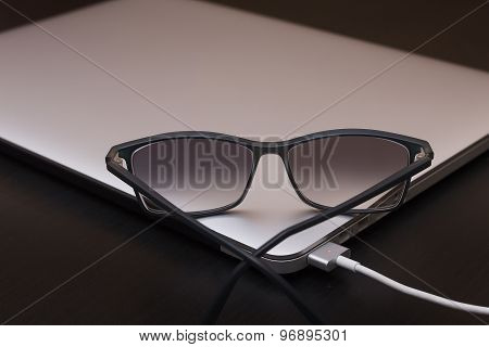 Glasses On The Charging Silver Laptop