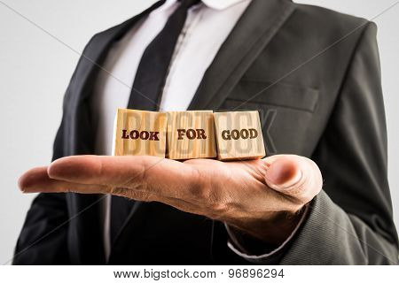 Closeup of male hand holding up three wooden cubes with a Look for good text. Conceptual of personal