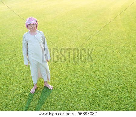 Arabian boy on grass meadow